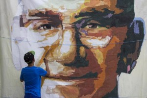 In this March 15, 2015 photo, a young man paints a portrait of Archbishop Oscar Arnulfo Romero as part of the preparations for the 35th anniversary of Romero's death in San Salvador, El Salvador. In 1980, Romero was assassinated while offering Mass. In 2015 Pope Francis declared that Romero died a martyr's death and he will be beatified later this year. (AP Photo/Salvador Melendez)