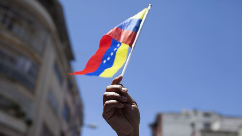 An opposition supporter waves a Venezuelan national flag as she attends a rally in Caracas