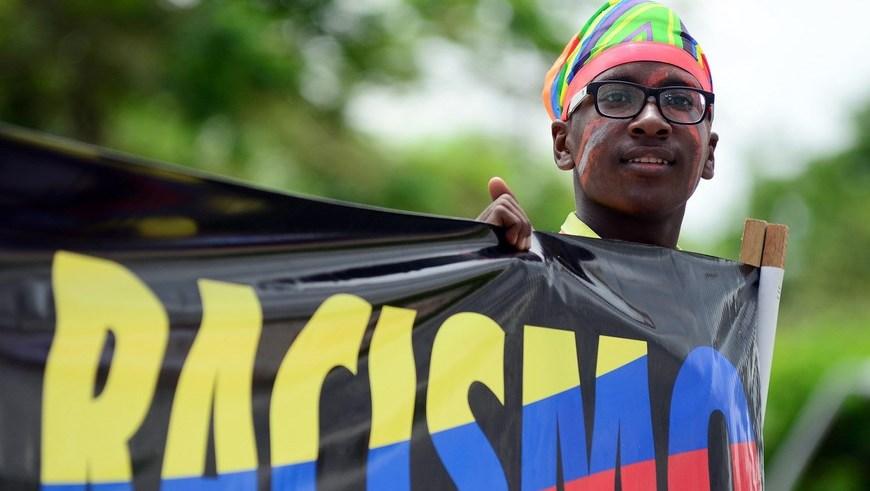 CAL34. CALI (COLOMBIA), 21/05/2015.- Un joven sostiene un pendón en el Día de la Afrocolombianidad hoy, jueves 21 de mayo de 2015 en Cali (Colombia). La Organización de las Naciones Unidas en Colombia celebró y apoyó hoy la entrada en vigencia del Decenio Internacional de los Afrodescendientes, que busca promover el respeto, la protección y la realización de los derechos humanos y libertades fundamentales de esta comunidad. La Asamblea General de la ONU proclamó este decenio, que comenzó el 1 de enero de 2015 y terminará el 31 de diciembre de 2024, para que la comunidad internacional reconozca los derechos fundamentales de los afrodescendientes que se registran en la Declaración Universal de Derechos Humanos. EFE/ERNESTO GUZMÁN JR