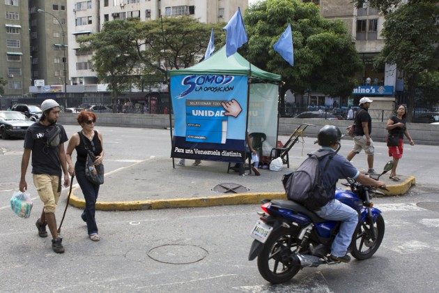 People pass by a tent for MIN Unidad Party in a main avenue in Caracas, November 3, 2015. Venezuela is projecting a drastic set of migration patterns in months leading up to the pivotal Dec. 6 parliament vote: a fiercely opposition district of the capital will lose a quarter of its population while pro-government suburbs will swell 5 percent. Picture taken November 3, 2015. REUTERS/Marco Bello