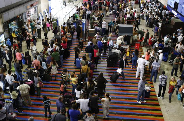 Passengers line up for the security checkpoint at Simon Bolivar airport in La Guaira
